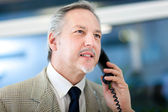 Mature businessman speaking at phone — Foto de Stock