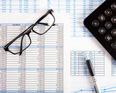 Calculator, eyeglasses and financial charts — Photo