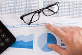Calculator, eyeglasses and financial charts — Stockfoto