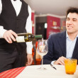 Waiter serving wine to man — Stock Photo #50348931