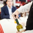 Waiter uncorking wine bottle — Stock Photo #50348947