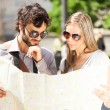 Happy tourists couple holding map — Stock Photo #50349207