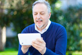 Dojrzały człowiek za pomocą tabletu — Zdjęcie stockowe
