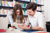 Students reading book in library — Stock Photo
