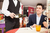 Waiter serving wine to man — Stock Photo