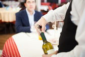 Waiter uncorking wine bottle — Стоковое фото