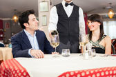 Waiter pouring wine in glass — Stock Photo