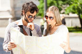 Happy tourists couple holding map — Stok fotoğraf