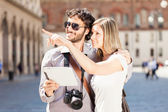 Tourists couple holding tablet — Stok fotoğraf