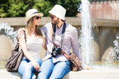 Tourists sitting next to fountain — Stock Photo