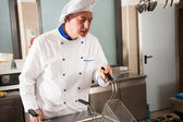 Male chef using deep fryer — Stock Photo