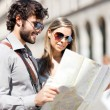 Couple of tourists holding map — Stock Photo #50353293