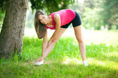 Young woman stretching outdor — Stockfoto