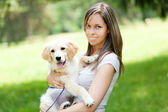Girl holding dog outdoors — Stock Photo
