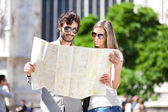 Tourists couple looking at map — Stock Photo