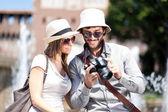Tourist showing photos to girlfriend — Stock Photo