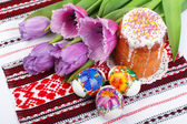 Easter eggs, cake and tulips on towel — Stock Photo