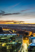 Sunset over the lighted city — Stock Photo