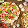 Closeup of baked and raw pizza with fresh ingredients — Stock Photo