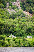 Houses on the cliff in the mountains by the lake — Стоковое фото