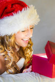 Young woman happily opens a gift — Stock Photo