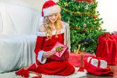 Beautiful woman opening a Christmas gift — Stock Photo