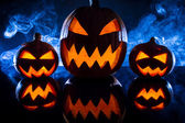 Three halloween pumpkins in the smoke background — Stock Photo