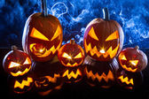 Group halloween pumpkins on the background smoke — Stock Photo