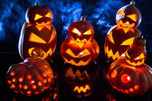 Group strange pumpkins on black background with smoke — Stock Photo