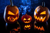 Three pumpkins and smoke on Halloween — Stock Photo