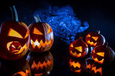 Small and large pumpkins for Halloween with candles on a black b — Stock Photo