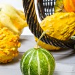 Close-up of an old wicker basket and a small colored pumpkins — Stock Photo #14296003