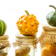 Stock Photo: Three small pumpkins on jars in basement