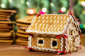 Homemade gingerbread cottage against a green Christmas tree — Stock Photo