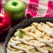 Two apples and freshly baked apple pie on tea towels — Stock Photo #16554387