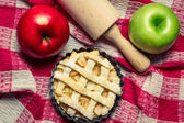 Apple pie with fruits and a rolling pin — Stock Photo
