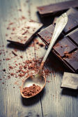 Cocoa Powder and Dark Chocolate on old table — Stock Photo