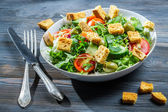 Caesar salad made of fresh vegetables on old table — Stock Photo