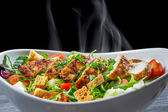 Close-up of hot chicken Caesar salad with vegetables — Stock Photo