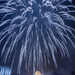 Stock Photo: Big spectacular fireworks over river at night