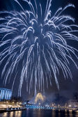Big spectacular fireworks over river at night — Stock Photo