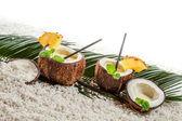Few pinacolada drinks in coconut on white beach — Stock Photo