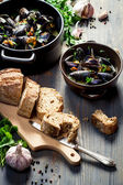 Mussels served with bread with garlic and parsley — Stock Photo