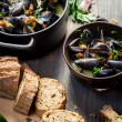 Closeup of Mussels served with bread with garlic and parsley - Stock Photo
