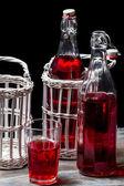 Alte flaschen im korb mit roten saft — Stockfoto