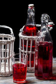 Old bottles in basket with red juice — Stock Photo