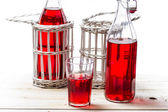 Closeup of red juice in old bottles on white background — Foto Stock