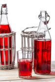 Vintage flaschen im korb mit saft auf weißem hintergrund — Stockfoto