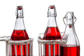 Drei alte flaschen mit roten saft — Stockfoto
