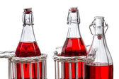 Três velhas garrafas com suco vermelho — Foto Stock